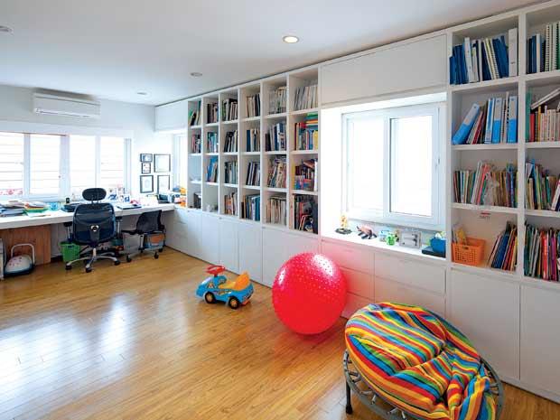 Phòng làm việc của bố mẹ đồng thời là phòng học và chơi của các con, nổi bật với kệ sách lớn và nhiều đồ chơi của bé.